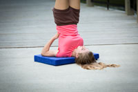 girl doing shoulderstand on platform