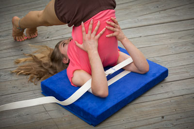 girl doing halasana using belt around arms