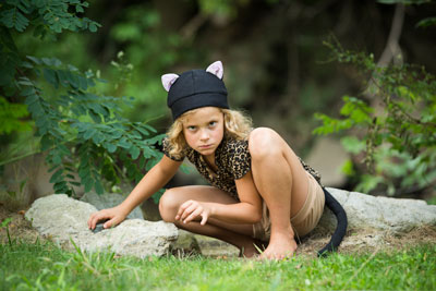 girl crouching wearing black cat hat and tail
