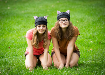 two teenagers wearing black cat hats